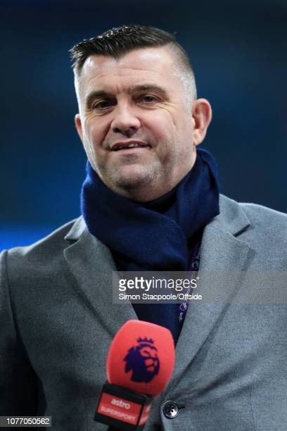 Former Liverpool player Dominic Matteo holds a microphone as he works as a television pundit during the Premier League match between Manchester City...