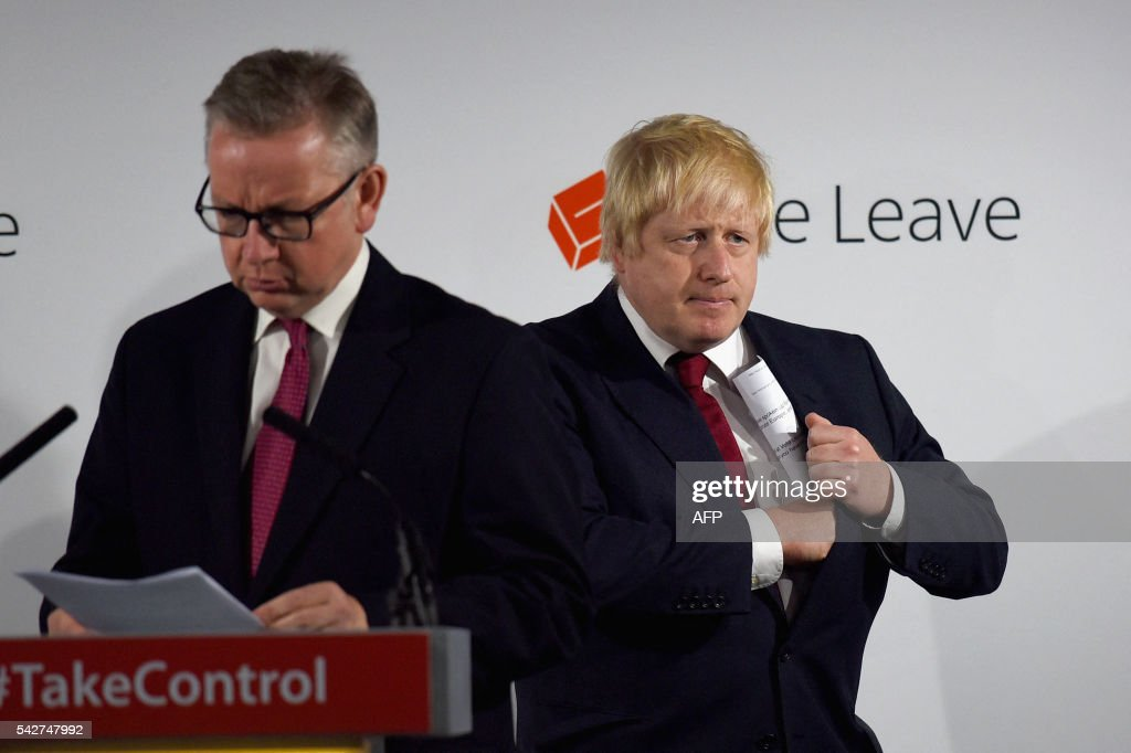 former London Mayor Boris Johnson (R) pockets his notes as fellow Vote Leave campaigner British Lord Chancellor and Justice Secretary Michael Gove (L) takes the podium to speak during a press conference at the Vote Leave headquarters in central London on June 24, 2016 after the UK voted to leave the European Union. Boris Johnson, who spearheaded the successful campaign for Britain to leave the European Union, said Friday there was no need to rush the process of pulling out of the bloc. / AFP / POOL / Mary Turner