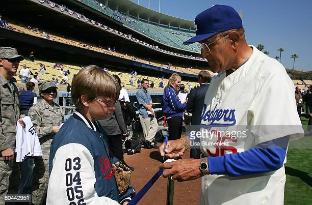 Former Los Angeles Dodger Don Newcombe signs autographs before the Dodgers Opening Day game against San Francisco Giants at Dodger Stadium on March...