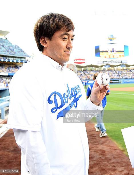 Former Los Angeles Dodgers Kazuhisa Ishii of Japan holds up a ball before taking to the mound to throw out a ceremonial first pitch before the game...