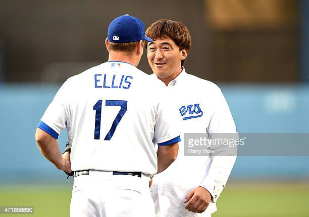 Former Los Angeles Dodgers Kazuhisa Ishii of Japan shakes hands with AJ Ellis after throwing a ceremonial first pitch before the game between the San...