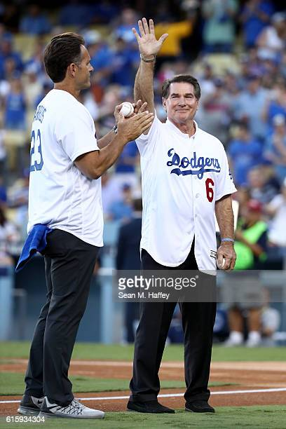 Former Los Angeles Dodgers Steve Garvey waves to the crowd as he stands alongside Eric Karros before the ceremonial first pitch before game five of...