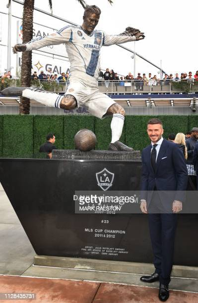 Former Los Angeles Galaxy midfielder David Beckham poses beside his newly unveiled statue at the Legends Plaza in Carson California on March 2 2019...