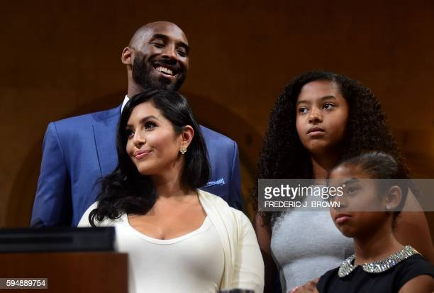 Former Los Angeles Laker Kobe Bryant standing with his family reacts to speeches being made at a city council meeting where he was honored with Kobe...