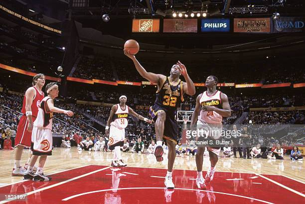 Former Los Angeles Laker Magic Johnson goes up for the shot during the NBA 2003 ALLSTAR Weekend Jeep ALLSTAR Hoop It Up Series at Philips Arena on...
