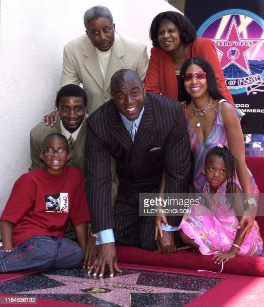 US former Los Angeles Lakers' basketball star Earvin Magic Johnson poses with his family son Earvin Jr son Andre father Earvin Sr mother Christine...