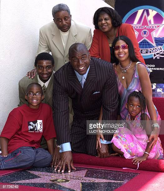 US former Los Angeles Lakers' basketball star Earvin 'Magic' Johnson poses with his family son Earvin Jr son Andre father Earvin Sr mother Christine...