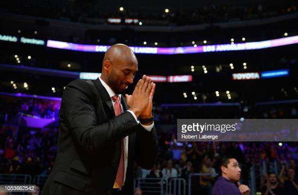 Former Los Angeles Lakers great Kobe Bryant gestures to the fans during the first half of the NBA game between the Denver Nuggets and the Los Angeles...