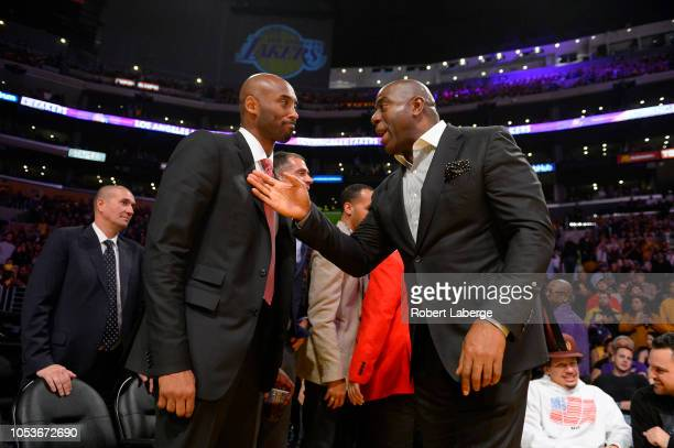 Former Los Angeles Lakers Kobe Bryant left and Earvin Magic Johnson president of basketball operations of the Lakers talk during the game between the...