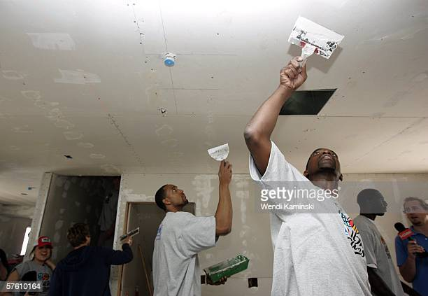 Former Los Angeles Lakers player AC Green and Tim Thomas of the Phoenix Suns work on Habitat for Humanity's housing project for Maritza Jacobo's new...