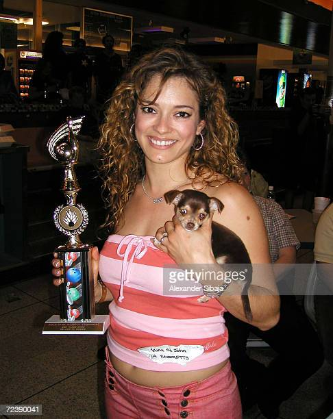 Former Los Angeles Raiders cheerleader Allana St John holds her trophy and a puppy chihuahua at the Celebrity Bowling Classic to benefit the Foothill...