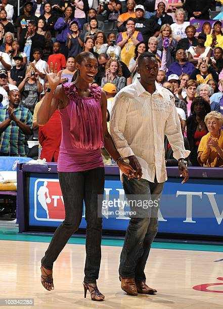 Former Los Angeles Sparks player Lisa Leslie and her husband Michael Lockwood walk to center court during a ceremony to retire her jersey at halftime...