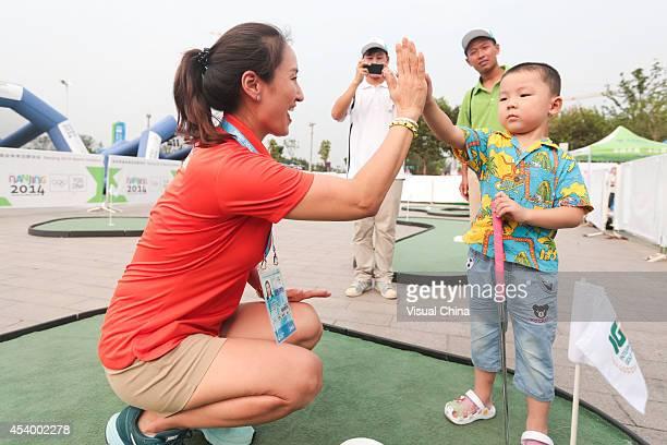 Former LPGA golfer Grace Park of South Korea highfives a boy during IGF Sport Initiation Programme Activities at WANDA Celebration Site on August 23...