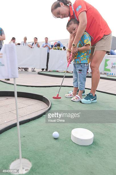 Former LPGA golfer Grace Park of South Korea instructs a boy in swing during IGF Sport Initiation Programme Activities at WANDA Celebration Site on...