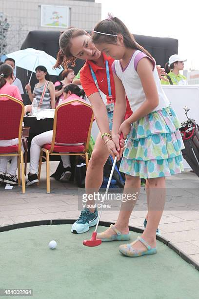 Former LPGA golfer Grace Park of South Korea instructs a girl in swing during IGF Sport Initiation Programme Activities at WANDA Celebration Site on...