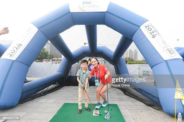 Former LPGA golfer Grace Park of South Korea poses with a boy during IGF Sport Initiation Programme Activities at WANDA Celebration Site on August 23...