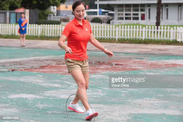 Former LPGA golfer Grace Park of South Korea rolls a hoop during IGF Sport Initiation Programme Activities at Nanjing Xuanwu Secondary Vocational...