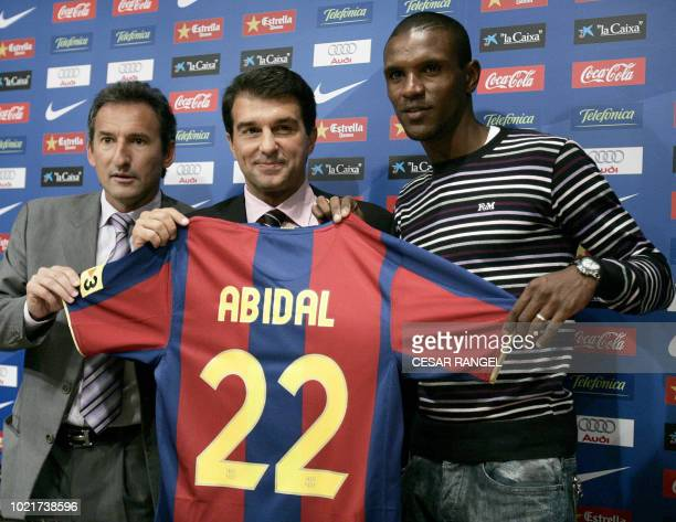 Former Lyon player Eric Abidal poses with Barcelana President Joan Laporta and Txiki Beguiristáin Barcelona's Director of Football during his...
