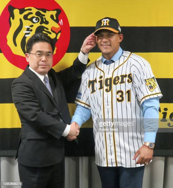 Former major league infielder Jefry Marte of the Dominican Republic poses for photos with Hanshin Tigers director Osamu Tanimoto in Nishinomiya,...