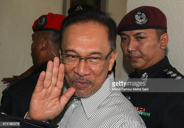 Former Malaysian opposition leader Anwar Ibrahim waves to supporters upon arrival at court for the defamation suit hearing against his former tennis...