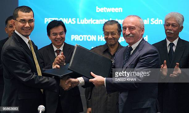 Former Malaysian premier Mahathir Mohamad witnesses a ceremony as Syed Zainal Abidin group managing director of Proton Holdings and Aldino Bellazzini...