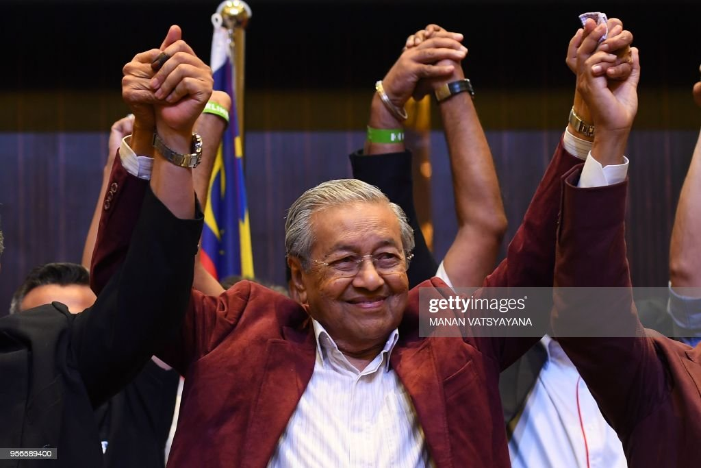 Former Malaysian prime minister and opposition candidate Mahathir Mohamad celebrates with other leaders of his coalition during a press conference in Kuala Lumpur on early May 10, 2018. - Malaysia's opposition alliance headed by veteran ex-leader Mahathir Mohamad, 92, has won a historic election victory, official results showed on May 10, ending the six-decade rule of the Barisan Nasional (BN) coalition.