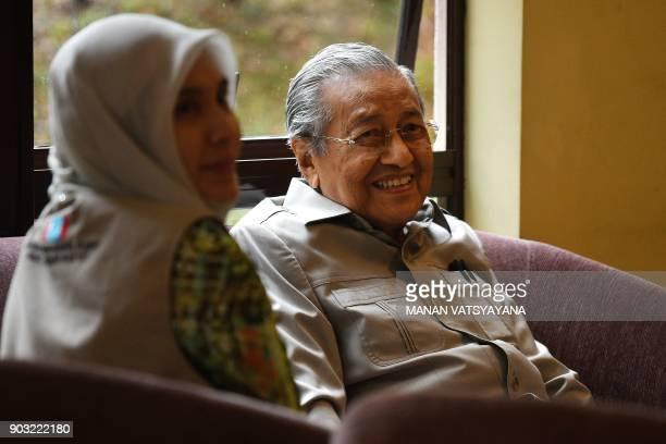 Former Malaysian prime minister and opposition's prime ministerial candidate Mahathir Mohamad talks with Nurul Izzah while waiting to visit her...