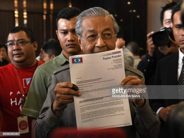 Former Malaysian prime minister and winning opposition candidate Mahathir Mohamad holds up a document addressed to the Yang diPertuan Agong the...