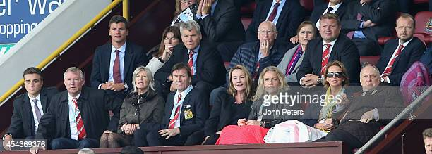 Former manager Sir Alex Ferguson of Manchester United watches from the directors box with his grandson Jake former Chief Executive David Gill Sir...