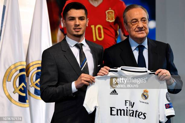 Former Manchester City's Spanish midfielder Brahim Diaz holds his new jersey with Real Madrid's president Florentino Perez during his oficial...