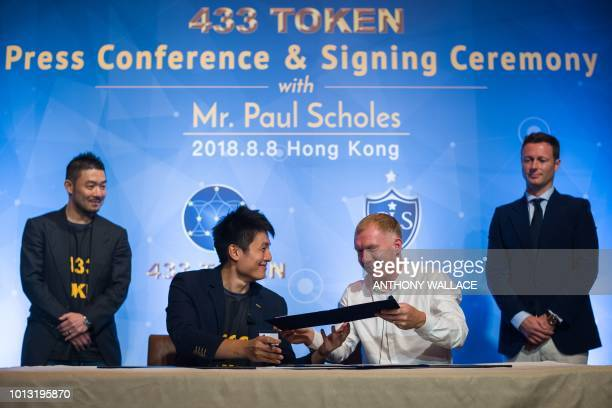 Former Manchester United and England football player Paul Scholes front R and Soccer Legends Ltd cofounder and CEO Jason Sze exchange signed...
