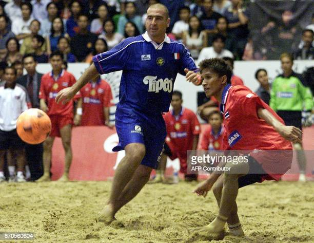 Former Manchester United football player Eric Cantona vies for the ball with Thai soccer player Surasak Tang Surat during beach soccer in Bangkok 12...