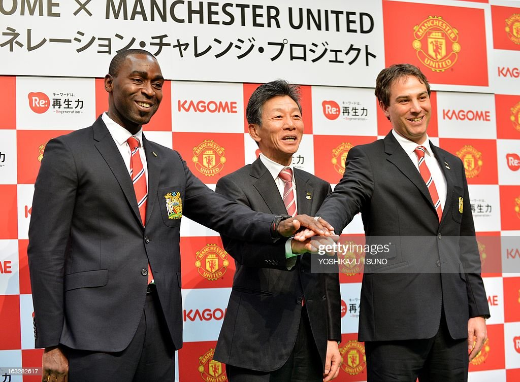 Former Manchester United forward Andy Cole (L), Manchester United Asia Pacific Director Jamie Reigle (R) and Japanese food company Kagome president Hidenori Nishi pose for a photograph at a press conference in Tokyo on March 7, 2013. Cole will foin Manchester United and Japanese food company Kagome during a football clinic for Japanese children living in the earthquake and tsunami stricken Tohoku region later this month. Manchester United will play a pre-season game against Japan's Yokohama F Marinos in Yokohama in July. AFP PHOTO / Yoshikazu TSUNO