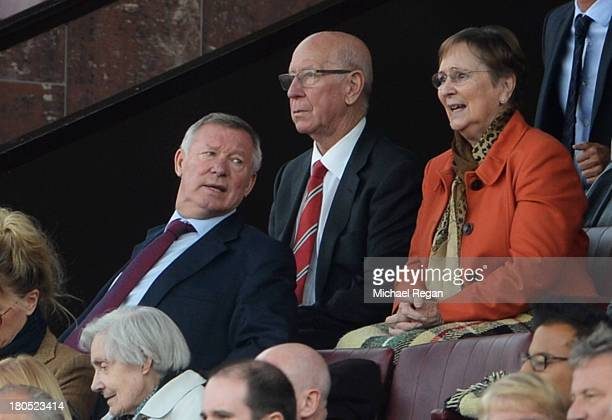 Former Manchester United manager Sir Alex Ferguson sits with Sir Bobby Charlton and his wife Norma during the Barclays Premier League match between...
