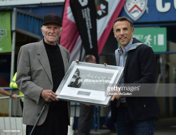 Former Manchester United player Phil Neville presents former Manchester United and Northern Ireland player Harry Gregg with a framed photograph of...