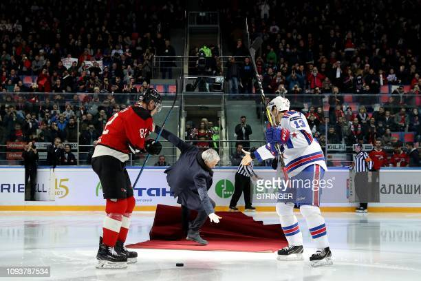 TOPSHOT Former Manchester United's Portuguese manager Jose Mourinho falls as he drops the puck to start a Continental hockey league match between...