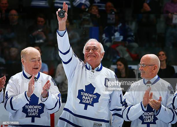 Former Maple Leafs Captain George Armstrong waves to the crowd in between Red Kelly and David Keon during a ceremony commemorating the 50th...