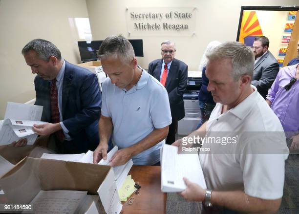 Former Maricopa County Sheriff Joe Arpaio watches as officials sort through stacks of petitions Arpaio submitted at the Arizona State Capitol while...