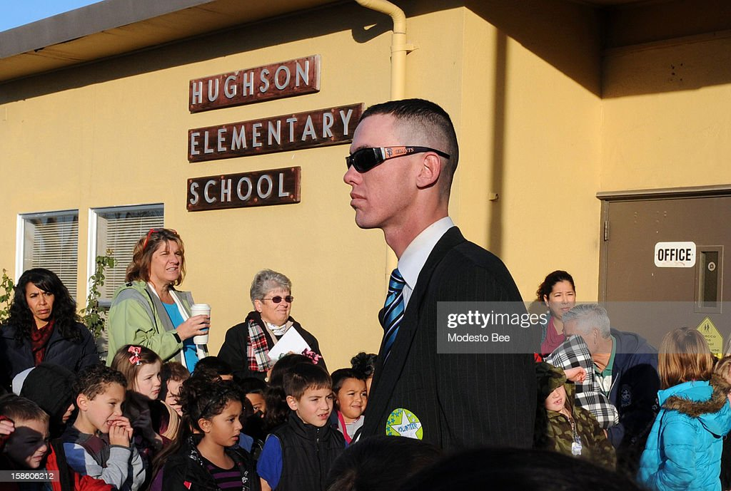 Former Marine Craig Pusley, who served only nine months before being discharged as a private first class in April 2008, greets children and parents at Hughson Elementary School before the start of classes on Thursday morning, December 20, 2012, in Hughson, California. The veteran who achieved national fame this week for guarding the elementary school had a far less distinguished service career than he has claimed in public, records obtained today show.