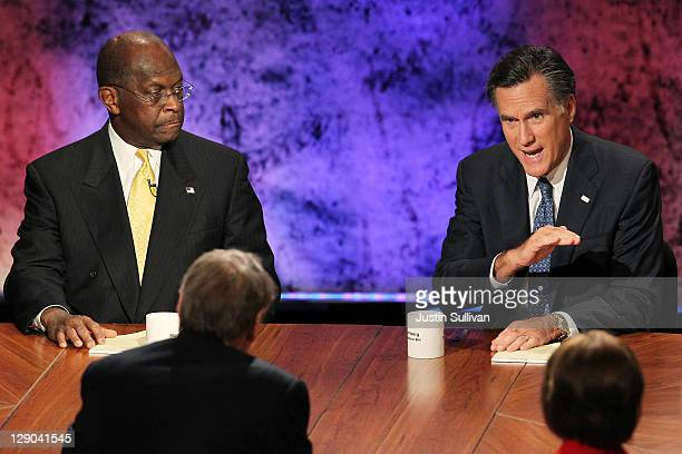 Former Massachusetts Gov Mitt Romney speaks as former CEO of Godfather's Pizza Herman Cain looks on during the Republican Presidential debate hosted...