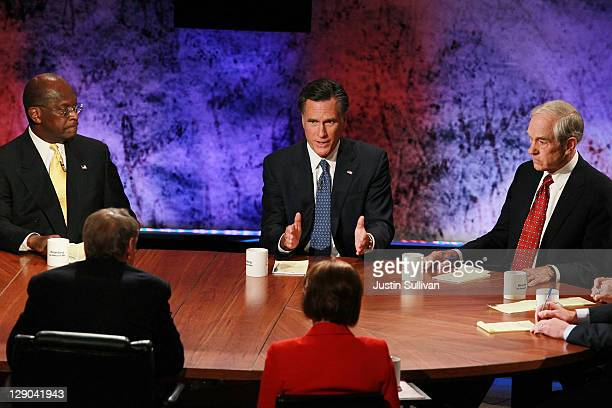 Former Massachusetts Gov Mitt Romney speaks as former CEO of Godfather's Pizza Herman Cain and US Rep Ron Paul look on during the Republican...