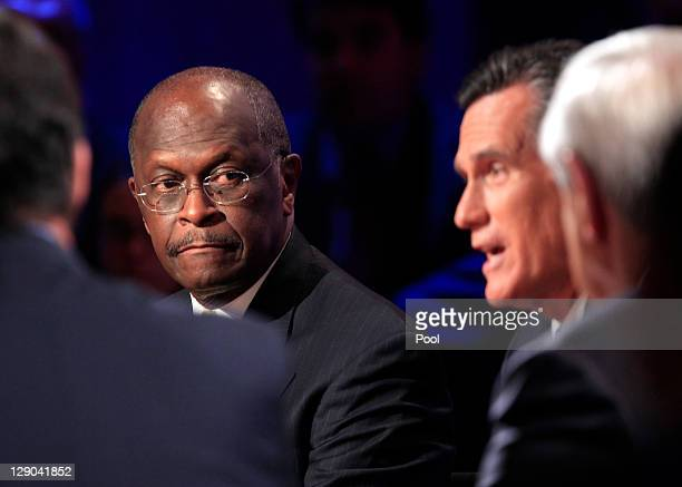 Former Massachusetts Gov Mitt Romney speaks while Herman Cain looks on during a presidential debate hosted by Bloomberg and the Washington Post on...