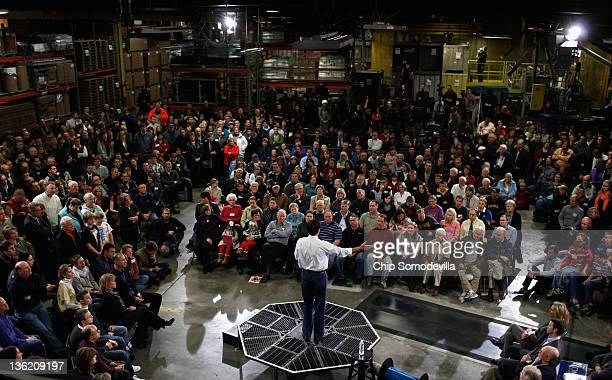 Former Massachusetts Governor and Republican presidential candidate Mitt Romney stands on a piece of industrial equipment while addressing a large...
