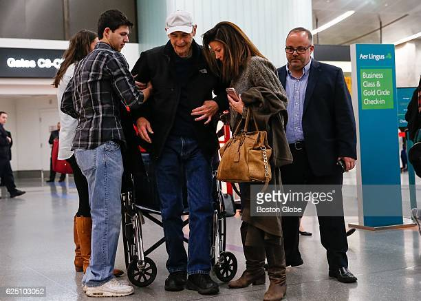 Former Massachusetts House Speaker Sal DiMasi is helped to his feet by his wife Debbie and son Christian as be leaves Logan International Airport in...