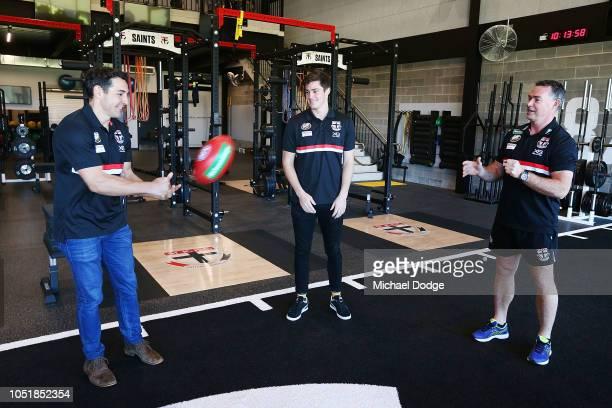 Former Melbourne Storm player Billy Slater handballs to Saints head coach Alan Richardson and Jack Steele of the Saints during a St Kilda Saints AFL...