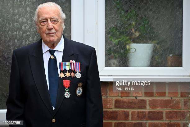 Former member of Britain's Royal Navy, Ray Smith, stands outside his home in Northampton, central England on November 8, 2020 to observe two minutes...
