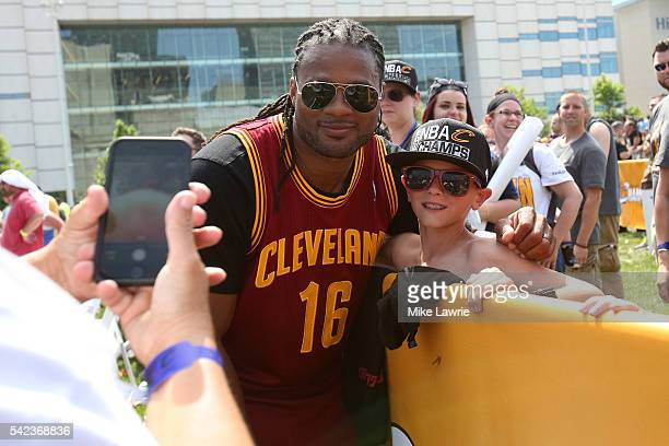 Former member of the Cleveland Browns Josh Cribbs poses with a fan during the Cleveland Cavaliers 2016 NBA Championship victory parade and rally on...