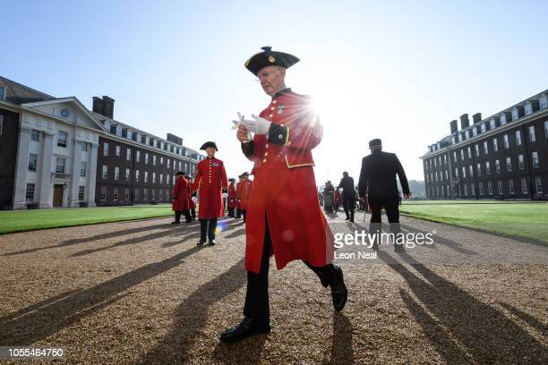 Former members of the armed forces, known as Chelsea Pensioners, wear their scarlet coats and tricorne hats as they leave the parade ground, after...