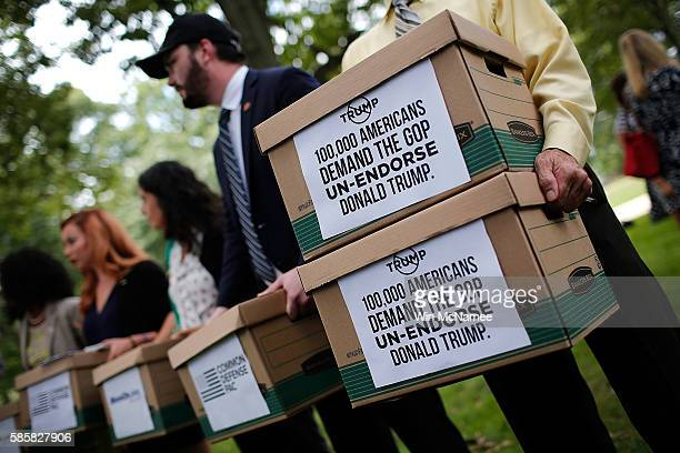 Former members of the US military carry boxes representing more than 100000 signatures requesting that Sen John McCain and other Republican leaders...