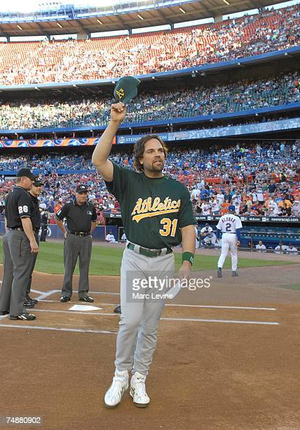 Former Met catcher Mike Piazza of the Oakland Athletics waves to the crowd after bringing out the lineup card before the game against the Mets at...